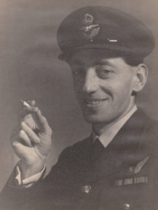 A picture of Arthur White in his uniform, smiling and holding a cigarette